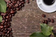 Hoogste mening van geroosterde koffiebonen met groene bladeren en mok sterke koffie op houten achtergrond Aromatische drank Geïso Stock Fotografie
