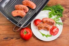Hoogste mening van geroosterde worsten met greens en tomaten stock fotografie