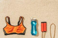 hoogste mening van geschikte sportkleding, touwtjespringen en waterfles op zand royalty-vrije stock afbeelding