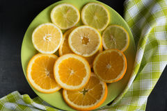 Hoogste mening van gesneden citrusvruchtencitroen, sinaasappel en daling op groene plaat over zwarte achtergrond Royalty-vrije Stock Fotografie