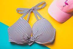 Hoogste mening van gestreepte blauwe en witte zwemmende bustehouder en roze strandhoed met flamingo op blauwe en gele pastelkleur Royalty-vrije Stock Fotografie