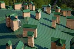 Hoogste mening van groen dak met oranje schoorstenen stock fotografie
