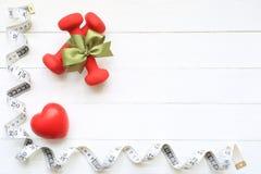 Hoogste mening van Groen lint met dumbells en het meten van band van gezond hart op houten witte achtergrond, Gezondheidszorgconc royalty-vrije stock foto