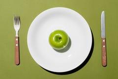 Hoogste mening van groene appel op witte plaat met mes en vork op gr. Stock Foto