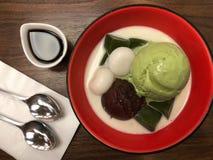 Hoogste mening van groene het roomijslepel van theematcha met rode bonenmochi en melk in rode kom Stock Foto