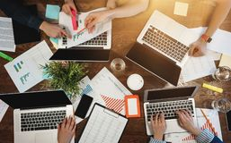 Hoogste mening van groeps bedrijfsmensen die bij lijst zitten en moderne laptop, grafieken en diagrammen gebruiken Het team van a stock foto's