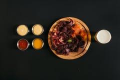 hoogste mening van heerlijk gesneden geassorteerd vlees op houten raad met glas bier en sausen stock fotografie