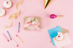 Hoogste mening van heerlijke cupcakes, kleurrijke kaarsen en decoratieve envelop op roze Royalty-vrije Stock Fotografie