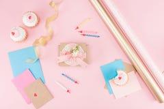 Hoogste mening van heerlijke cupcakes, kleurrijke kaarsen en decoratieve envelop op roze Stock Afbeeldingen