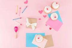 Hoogste mening van heerlijke cupcakes, kleurrijke kaarsen en hartensymbolen op roze Stock Foto's