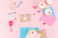 Hoogste mening van heerlijke cupcakes, kleurrijke kaarsen en hartensymbolen op roze Stock Afbeelding