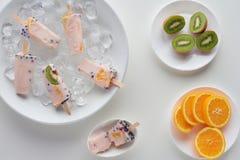 hoogste mening van heerlijke eigengemaakte ijslollys met ijsblokjes en gesneden kiwi en sinaasappel royalty-vrije stock afbeelding