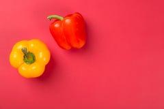 Hoogste mening van heldere gele en rode groene paprika'spaprika op rode achtergrond Stock Foto's