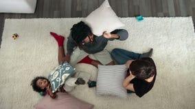 Hoogste mening van het gelukkige familiehoofdkussen vechten op tapijt stock video