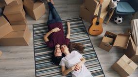 Hoogste mening van het gelukkige man en vrouwen spreken die op tapijt in nieuwe vlakte met dozen liggen stock footage