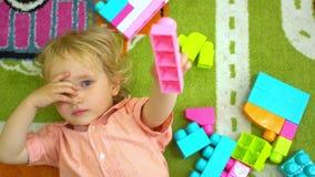 Hoogste mening van het leuke kind spelen met multi gekleurde bouwstenen in peuterkindontwikkeling in kleuterschool stock footage