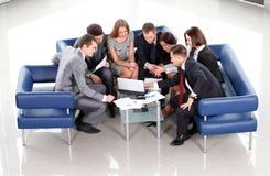 Het werk commerciële groepszitting bij lijst tijdens collectieve vergadering Stock Afbeeldingen