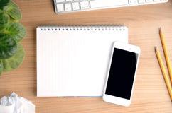 Hoogste mening van het werk ruimte met smartphone over een lege blocnote Stock Foto's