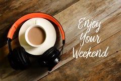 Hoogste mening van hoofdtelefoons en een kop van koffie op houten die achtergrond met ENJOY wordt geschreven UW WEEKEND stock foto's