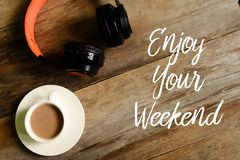 Hoogste mening van hoofdtelefoons en een kop van koffie op houten die achtergrond met ENJOY wordt geschreven UW WEEKEND royalty-vrije stock afbeeldingen