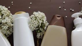 Hoogste mening van hygiënisch/cosmetische product en bloemen op bruine achtergrond De behandeling van de Wellnessschoonheid stock video