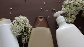 Hoogste mening van hygiënisch/cosmetische product en bloemen op bruine achtergrond De behandeling van de Wellnessschoonheid stock videobeelden
