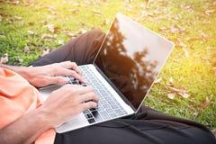 Hoogste mening van jonge mensenzitting in park op groen gras met laptop Stock Foto