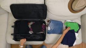 Hoogste mening van jonge vrouw die kleren organiseren in een koffer stock videobeelden
