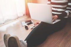 Hoogste mening van jonge vrouwenzitting op vloer met laptop, Laptop in meisjes` s handen die op een houten vloer zitten stock foto