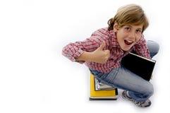 Hoogste mening van jongenszitting op stapel van boeken stock afbeelding