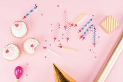 Hoogste mening van kleine giftdoos, kleurrijke kaarsen en heerlijke cupcakes op roze Royalty-vrije Stock Fotografie
