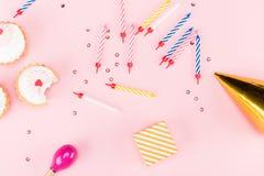 Hoogste mening van kleine giftdoos, kleurrijke kaarsen en heerlijke cupcakes op roze Stock Foto