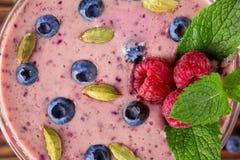 Hoogste mening van kleurrijke smoothiecocktail als achtergrond Verfrissende drank met rijpe heldere bessen, zaden en muntbladeren Royalty-vrije Stock Foto