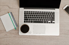 Hoogste mening van laptop, een slimme telefoon, een notitieboekje met een potlood en een kop van koffie Stock Foto