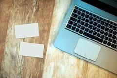 Hoogste mening van laptop en lege adreskaartjes op bureau stock foto's