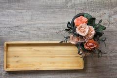 Hoogste mening van leeg houten vierkant dienblad en kunstbloem backg Stock Foto