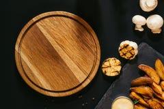 hoogste mening van lege houten raad, geroosterd knoflook, paddestoelen en aardappelen in de schil met saus royalty-vrije stock foto's