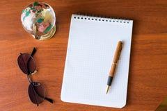 Hoogste mening van Lege notitieboekje Witboek en bol, zwarte glazen, wereldkaart op houten achtergrond met ruimte voor uw bericht stock foto's