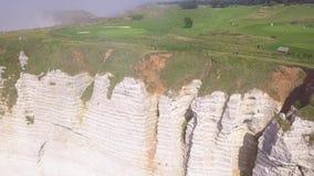 Hoogste mening van lopende toeristen op groene piek bij klip van witte klip actie Toneel hoogste mening van kustklip met lijnen stock video