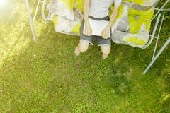 Hoogste mening van mannelijke freelancerzitting op de schommelingslaag bij de toevlucht van de de zomervakantie op gras stock afbeelding