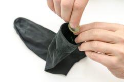 Mannelijke hand die Euro muntstuk zetten in een sok royalty-vrije stock afbeelding