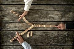 Hoogste mening van mannelijke hand duwende die domino's in y-vorm het kloppen worden geplaatst Stock Fotografie