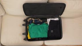 Hoogste mening van mannelijke handen die kleren inpakken en een koffer voor reis voorbereiden stock video