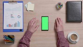 Hoogste mening van mannelijke vingers die binnen en uit het groen scherm van een smartphone zoemen stock footage
