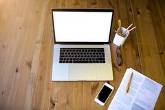 Hoogste mening van moderne werkplaats met document documenten, glazen, mobiele telefoon, potloden en draagbare laptop computer stock fotografie