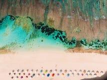 Hoogste mening van mooi zandstrand met turkoois zeewater en kleurrijke paraplu's, luchthommelschot stock foto