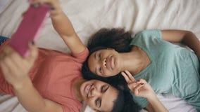 Hoogste mening van mooie gemengde ras grappige meisjes die selfie portret op bed in slaapkamer thuis maken stock videobeelden
