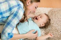 Hoogste mening van mooie vrouw en haar zoon die van de peuterbaby terwijl het liggen op de vloer glimlachen stock foto's