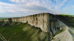 Hoogste mening van mooie witte rots met groen gras op achtergrond van blauwe hemel schot Panorama van witte klip met groen stock footage
