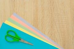 Hoogste mening van multicolored document en scisors op houten lijst Hoogste mening Regeling voor het creatieve werk of ambacht royalty-vrije stock foto